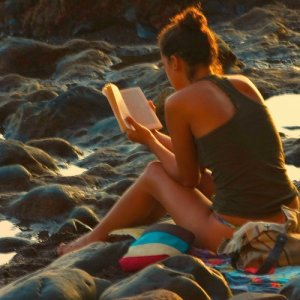 A young woman reads a book near the ocean as the sun sets.