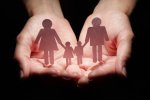 Stock image of two open palms holding a shadow family.