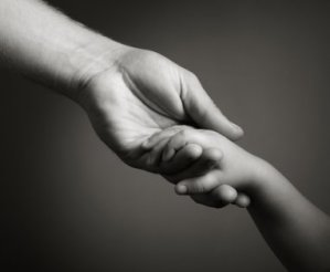 Black and white stock image of an adult holding a child's hand.