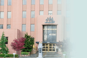 A medium shot of the Clark County Courthouse in Vancouver, Washington - a multi-story building with an light-red stone facade