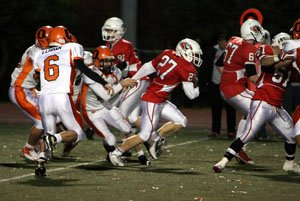 LHS football player running with ball down the field.