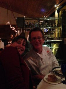 Woman smiling next to chef in restaurant.