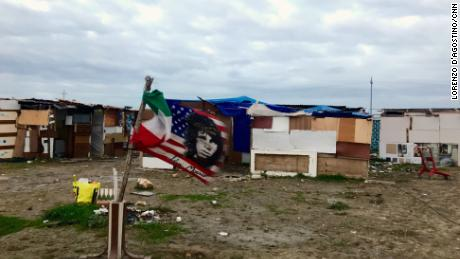 """A US flag bearing Jim Morisson's face flies next to an Italian flag, amid the makeshit homes of the """"Runway Ghetto,"""" in Foggia."""