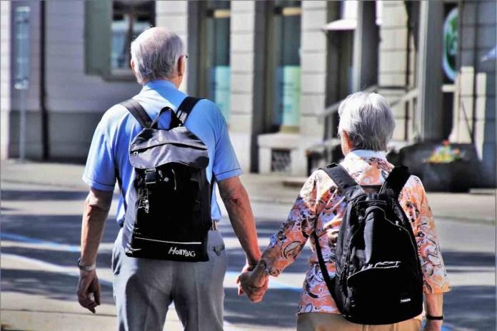 Coppia di anziani mano nella mano da dietro