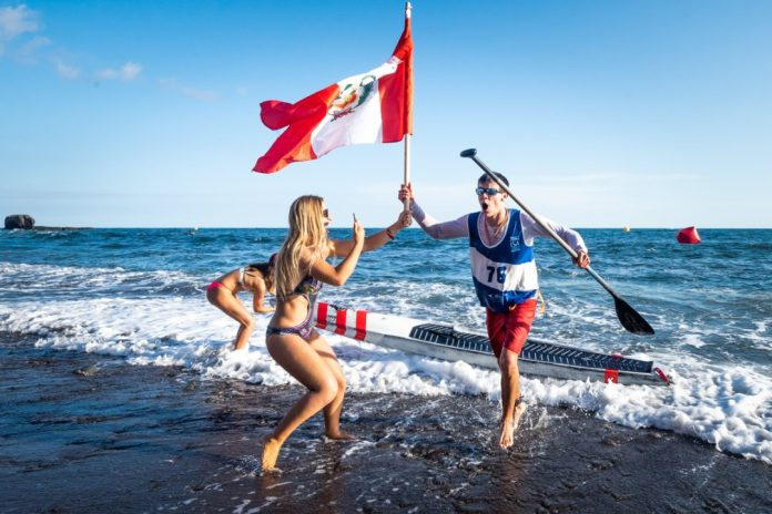 Itzel Delgado is handed his homeland flag for Peru upon his win at the ISA World Championships.