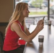 girl using a phone while having a coffee