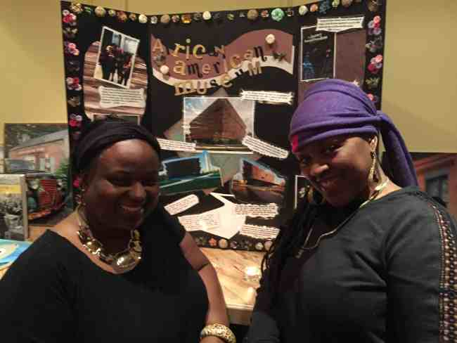 Coleta Walker and Jacqueline Renaud-Rivera standing in front of the museum poster board.