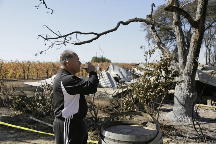 ASSOCIATED PRESS / NOV. 6 Izzy Lewkosky, of Kansas City, Kan., tastes a glass of Cabernet Sauvignon while looking out at the wildfire incinerated Soda Rock Winery in Healdsburg, Calif. Despite a late October blaze that raged through one of the world's best-known wine-growing regions, forcing evacuations in two mid-sized towns, wine production in Sonoma County escaped largely unscathed.