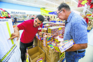 DENNIS ODA / DODA@STARADVERTISER.COM                                 People with permits are able to buy firecrackers at the Kaheka Street Don Quijote store. Anuenue Tui, left, helped Bill Pack buy the right amount of firecrackers with his permit.