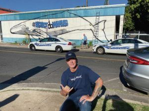 COURTESY WYLAND                                 Painter Robert Wyland posed for a photo Monday with his unauthorized mural of a whale on Dickenson Street in Lahaina, Maui.