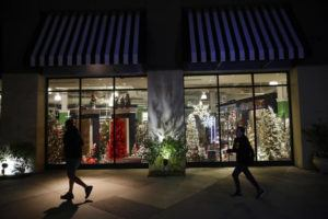 ASSOCIATED PRESS                                 Shoppers walk past a storefront with seasonal holiday products in Santa Clarita, Calif., on Dec. 16.