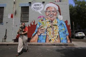 STEVEN SAPHORE/AAP IMAGES VIA AP                                 A mural depicting Prime Minister Scott Morrison wearing an unbuttoned Hawaiian shirt, orange lei and Santa Claus hat while holding a cocktail by artist Scott Marsh is seen on a wall in Sydney. Morrison was under pressure since taking a much criticized family vacation to Hawaii during the wildfire crisis.