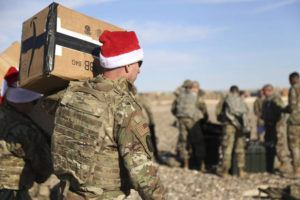 ASSOCIATED PRESS / DEC. 23 A U.S. soldier carries Christmas gifts from a helicopter to deliver to his comrades on a base near the al-Omar oilfield in eastern Syria. It's an operation is called Holiday Express — in addition to delivering presents, the U.S.-led coalition forces brought a U.S. military band to play Christmas carols and music to several bases in eastern Syria.