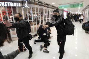 ASSOCIATED PRESS                                 An undercover policeman points a can of pepper spray as others detain a protester during a demonstration at a shopping mall popular with traders from mainland China near the Chinese border in Hong Kong.