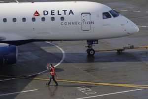 ASSOCIATED PRESS                                 In this Feb. 5, 2019, file photo a ramp worker guides a Delta Air Lines plane at Seattle-Tacoma International Airport in Seattle.