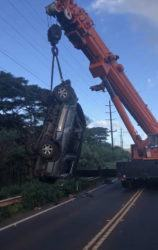 COURTESY KAUAI POLICE DEPARTMENT                                 A crane was used to remove an SUV that crashed early this morning on Kauai's Kaumualii Highway, injuring four men.