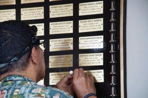 "CRAIG T. KOJIMA / CKOJIMA@STARADVERTISER.COM                                 Officer Dana Fatu, curator of the Honolulu Police Department museum, added officers Tiffany Enriquez and Kaulike Kalama to the ""Roll of Honor"" plaque Wednesday."