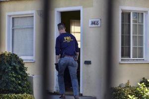 ASSOCIATED PRESS                                 An FBI evidence response team agent enters a building on the grounds of the Kingdom of Jesus Christ Church in the Van Nuys section of Los Angeles today. The FBI raided a Philippines-based church in Los Angeles to arrest leaders of an alleged immigration fraud scheme that resulted in sham marriages.