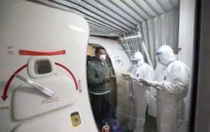CHINATOPIX VIA ASSOCIATED PRESS                                 Quarantine workers in protective suits checked identity documents as tourists from the Wuhan area walked off of a chartered plane taking them home from Bangkok at Wuhan Tianhe International Airport in Wuhan in central China's Hubei Province, today.