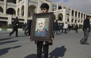 ASSOCIATED PRESS                                 A boy carries a portrait of Iranian Revolutionary Guard Gen. Qassem Soleimani, who was killed in a U.S. airstrike in Iraq, prior to the Friday prayers in Tehran, Iran.