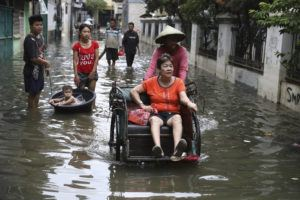ASSOCIATED PRESS                                 A woman rides a tricycle on a flooded street in Jakarta, Indonesia. Monsoon rains and rising rivers submerged parts of greater Jakarta and caused landslides in Bogor and Depok districts on the city's outskirts as well as in neighboring Lebak, which buried a number of people.
