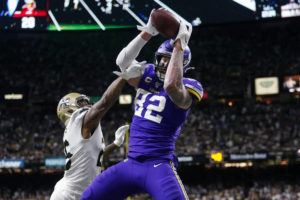 ASSOCIATED PRESS Minnesota Vikings tight end Kyle Rudolph (82) pulls in the game winning touchdown pass over New Orleans Saints cornerback P.J. Williams (26) during overtime of an NFL wild-card playoff football game today.