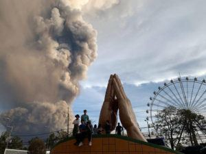 ASSOCIATED PRESS                                 People watch as the Taal volcano spews ash and smoke during an eruption in Tagaytay, Cavite province south of Manila, Philippines, today. A tiny volcano near the Philippine capital that draws many tourists for its picturesque setting in a lake belched steam, ash and rocks in a huge plume, prompting thousands of residents to flee and officials to temporarily suspend flights.