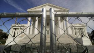 DEAN HOFFMEYER/RICHMOND TIMES-DISPATCH VIA AP                                 The Virginia state Capitol building is surrounded by fencing in Richmond, Va., in preparation for Monday's rally by gun rights advocates. Gun-rights groups are asking a judge to block the Virginia governor's ban on firearms at a massive pro-gun rally scheduled for next week. Gov. Ralph Northam on Wednesday, Jan. 15, announced a state of emergency and banned all weapons from the rally at the Capitol. |