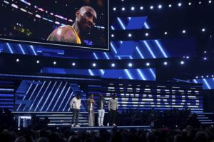 INVISION / AP                                 Nathan Morris, from left, Wanya Morris, Shawn Stockman, of Boyz II Men, and Alicia Keys, second left, sing a tribute in honor of the late Kobe Bryant, seen on screen, at the 62nd annual Grammy Awards today.