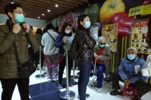 ASSOCIATED PRESS                                 People queue up waiting to purchase face masks outside a shop in Hong Kong on Wednesday.