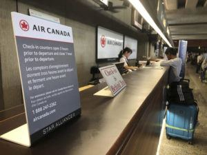 ASSOCIATED PRESS                                 Passengers stand in line at the Air Canada counter at Daniel K. Inouye International Airport. A passenger who died aboard an Air Canada flight on Saturday was identified today.