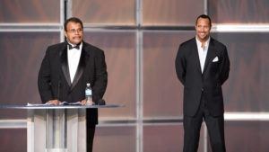 """WWE, INC. VIA AP / 2008                                 Rocky """"Soul Man"""" Johnson, left, speaks at his WWE Hall of Fame induction ceremony, as his son, Dwayne """"The Rock"""" Johnson watches. Rocky Johnson died Wednesday, Jan. 15. He was 75."""