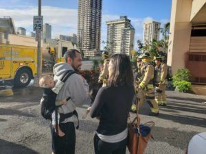 DENNIS ODA / DODA@STARADVERTISER.COM                                 Chad Goldstein, 10-month-old Evan Goldstein and Lisa Chau waited outside their Ala Wai Manor building as Honolulu firefighters battled a fire at the McCully condo.