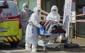 KIM JONG-UN/YONHAP VIA ASSOCIATED PRESS                                 Medical workers wearing protective gear moved a patient suspected of contracting the new coronavirus, Wednesday, from an ambulance to the Kyungpook National University Hospital in Daegu, South Korea.