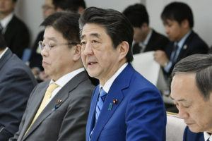 KYODO NEWS VIA AP                                 Japan's Prime Minister Shinzo Abe, center, speaks during a meeting of a task force on the new coronavirus at his official residence in Tokyo today. Abe asked all elementary, middle and high schools to remain shut until spring holidays begin in late March.