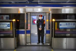 ASSOCIATED PRESS                                 A security officer wearing a face mask stood on a subway train, Monday, in Beijing. Health authorities are preparing for a possible pandemic as they work to contain a respiratory illness in China that's caused by a new virus.