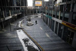 ASSOCIATED PRESS                                 A cleaner walks through a deserted compound of a commercial office building in Beijing.