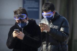 ASSOCIATED PRESS                                 Travelers wear face masks and goggles as they use their smartphones outside the Beijing Railway Station in Beijing.