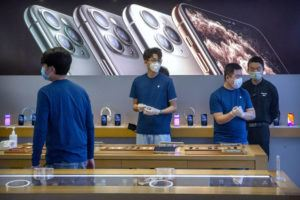 ASSOCIATED PRESS Employees wear face masks as they stand in a reopened Apple Store in Beijing on Feb. 14. Apple Inc. is warning investors that it won't meet its second-quarter financial guidance because the viral outbreak in China has cut production of iPhones.