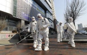 YONHAP VIA ASSOCIATED PRESS                                 Workers wearing protective gears spray disinfectant against the new coronavirus in front of a church in Daegu, South Korea, Thursday.