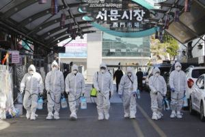 "ASSOCIATED PRESS                                 Workers wearing protective gears spray disinfectant as a precaution against the COVID-19 at a local market in Daegu, South Korea, today. South Korea's president has put the country on its highest alert for infectious diseases and says officials should take ""unprecedented, powerful"" steps to fight a viral outbreak."