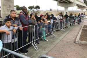 ASSOCIATED PRESS / 2019 Asylum seekers, in Tijuana, Mexico, listen to names being called from a waiting list to claim asylum at a border crossing in San Diego. A federal appeals court has temporarily halted a major Trump administration policy to make asylum seekers wait in Mexico while their cases wind through U.S. immigration courts. A panel of the 9th U.S. Circuit Court of Appeals in San Francisco ruled Friday, Feb. 28 in a 2-1 vote to put on hold the policy that furthered President Donald Trump's asylum crackdown.
