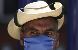 ASSOCIATED PRESS A street vendor wears a mask over his mouth as a precaution against the spread of the new coronavirus in Mexico City. Mexico's assistant health secretary announced Friday that the country now has confirmed cases of the COVID-19 virus.