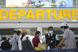 ASSOCIATED PRESS                                 Tourists wearing face masks line up to a departure gate at Bali airport, Indonesia on Saturday.