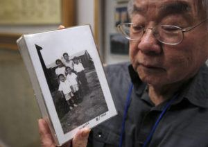 "ASSOCIATED PRESS / FEB. 11                                 Les Ouchida holds a 1943 photo of himself, front row, center, and his siblings taken at the internment camp his family was moved to, as he poses at the permanent exhibit titled ""UpRooted Japanese Americans in World War II"" at the California Museum in Sacramento, Calif. Ochida, who is a docent for the exhibit, and his family were forced to move in 1942 from their home near Sacramento to a camp in Jerome, Arkansas."