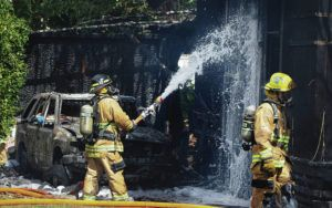 BRUCE ASATO / BASATO@STARADVERTISER.COM                                 Firefighters train their hoses on hot spots on the wall of the structure in front of a burned out vehicle.