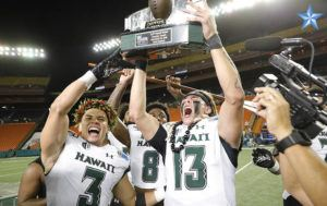 JAMM AQUINO / Dec. 24                                 Hawaii quarterback Cole McDonald (13) holds the championship trophy after winning the 2019 SoFi Hawaii Bowl college football game against the Brigham Young Cougars at Aloha Stadium in December. McDonald has been invited to compete at the NFL Scouting Combine in Indianapolis.