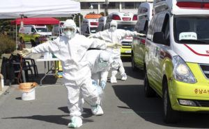 "KIM HYUN-TAI/YONHAP VIA ASSOCIATED PRESS Paramedics wearing protective gear were disinfected near their ambulances in Daegu, South Korea, today. Seoul expressed ""extreme regret"" Friday over Japan's ordering 14-day quarantines on all visitors from South Korea due to a surge in viral infections and warned of retaliation if Tokyo doesn't withdraw the restrictions."