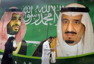 ASSOCIATED PRESS                                 People walk past a banner showing Saudi King Salman, right, and his Crown Prince Mohammed bin Salman, outside a mall in Jiddah, Saudi Arabia on Saturday.