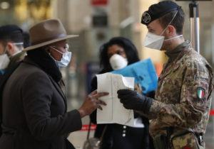 ASSOCIATED PRESS                                 Police officers and soldiers checked passengers leaving from Milan's main train station, in Italy, today. Italy took a page from China's playbook Sunday, attempting to lock down 16 million people — more than a quarter of its population — for nearly a month to halt the relentless march of the new coronavirus across Europe.